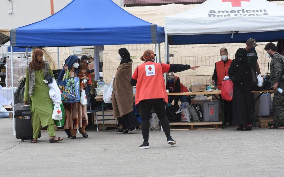 Volunteers with the American Red Cross hand out care packages and assist new arrivals from Afghanistan, Aug. 26, 2021. Ramstein was expecting about 10,000 more evacuees overnight Thursday. Some evacuees were to be housed temporarily at Rhine Ordnance Barracks, a neighboring Army base.