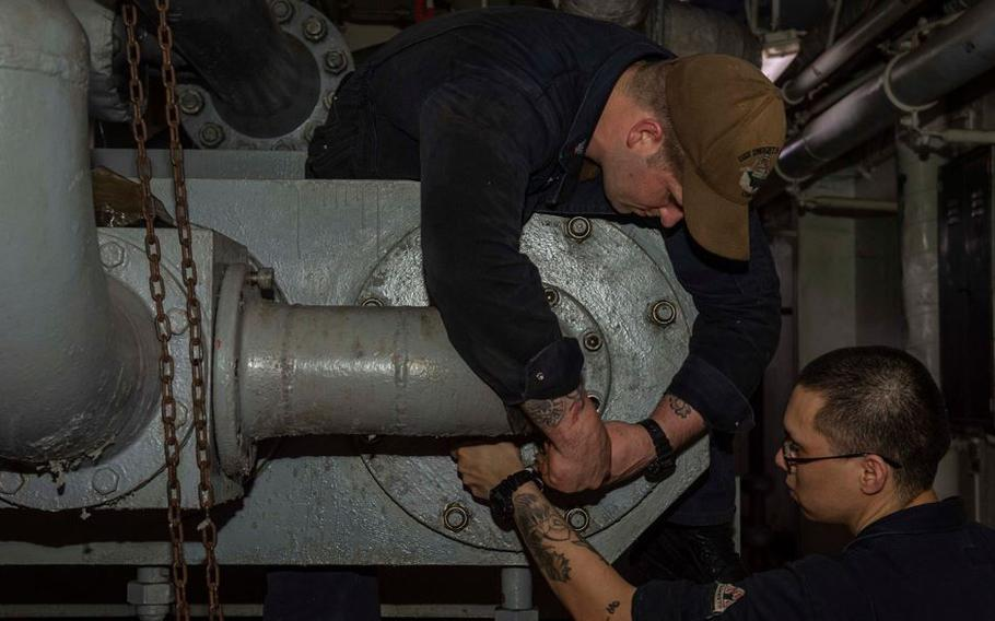 Petty Officer 1st Class Victor Herring Logam, left, and Petty Officer 2nd Class Luis Guzman remove a pipe from an aircraft elevator hydraulic pump aboard the aircraft carrier USS Dwight D. Eisenhower in the Arabian Sea, on May 28, 2021.
