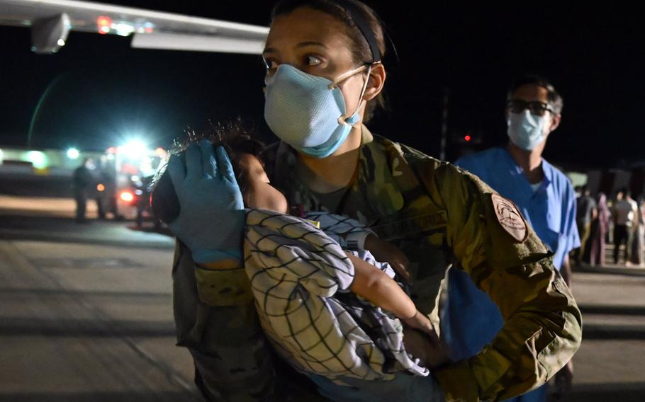 U.S. Air Force Tech. Sgt. Angie Smith carries a sleeping baby down from an Airbus A320 aircraft carrying evacuees from Afghanistan to Naval Air Station Sigonella, Italy, Aug. 29, 2021.