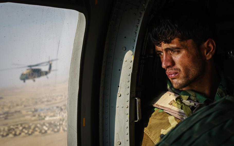 A soldier surveys the terrain out the window during a resupply flight on a UH-60 Blackhawk toward an outpost in the Shah Wali Kot district north of Kandahar, Afghanistan, on May 6, 2021.