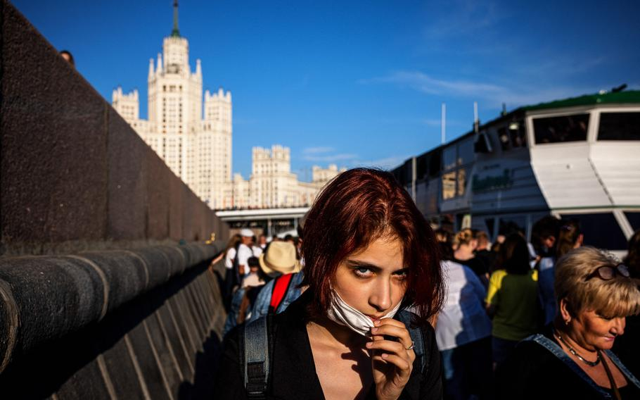 A woman adjusts her protective face mask while waiting to board a cruise boat trip along the Moskva river in Moscow on June 13, 2021.