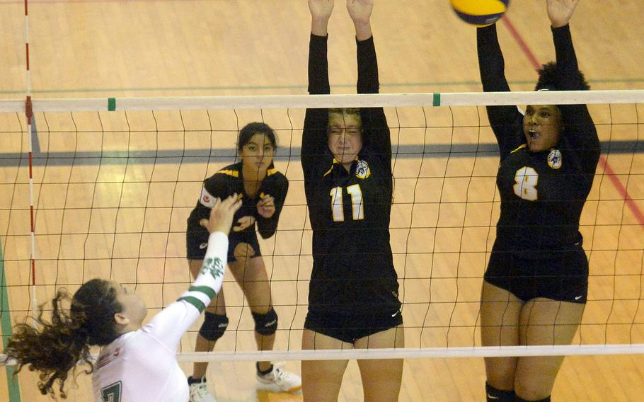 Kubasaki's Sophia Grubbs spikes past the double block of Kadena's Presley Pearce and Kimberly Wright during Thursday's Okinawa girls volleyball match. The Dragons won in three sets.