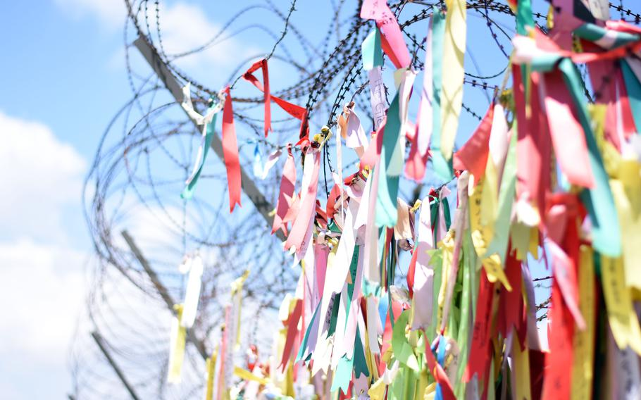 Buddhist prayer ribbons hang from a security fence in Paju, South Korea, near the Demilitarized Zone.