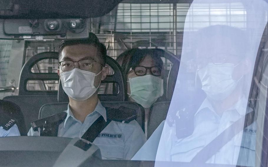"""Chow Han Tung, vice chairwoman of the Hong Kong Alliance in Support of Patriotic Democratic Movements of China, center, is escorted by police in a van to a court, in Hong Kong, Friday, Sept. 10, 2021 as she was charged with """"inciting subversion of state power"""" under the national security law."""