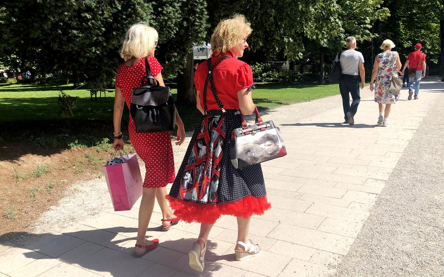 A woman carrying a handbag and wearing a petticoat swing dress with pictures of Elvis Presley walks with another woman through a park in Bad Nauheim, Germany, on Aug. 15, 2021. The spa town hosts a festival in August in honor of Presley, who lived in Bad Nauheim when he was a U.S. Army private from 1958-1960.