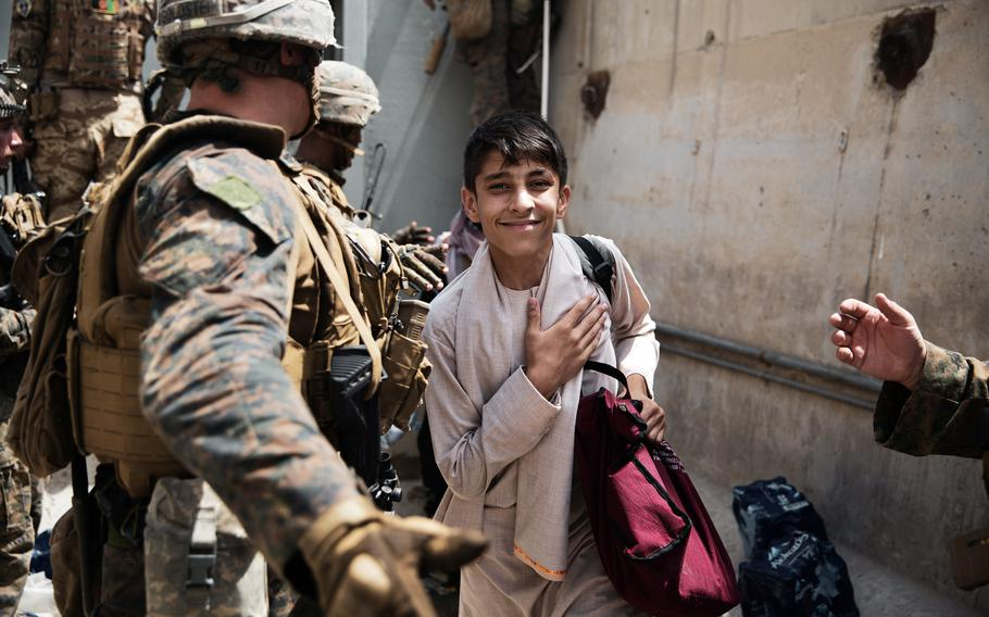 A boy is processed through a checkpoint during an evacuation at Hamid Karzai International Airport, Kabul, Afghanistan, Aug. 18, 2021.