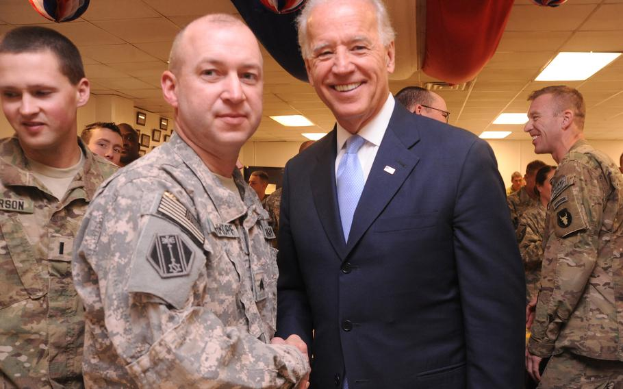 Sgt. Arther Rehkopt, 46th Military Police Command, shakes hands with Vice President Joe Biden at Bagram Airfield, Afghanistan in December 2011. As president, Biden ordered the complete withdrawal of U.S. troops from Afghanistan by Sept. 11, 2021.