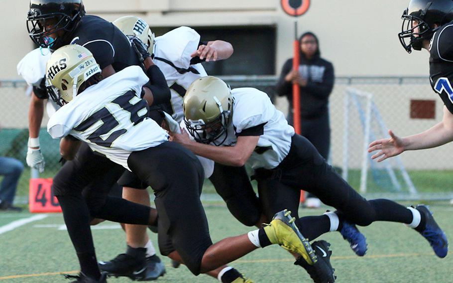 Osan running back Jaylon Grant drags Humphreys defenders Emmanuel Lawson and Luke Robinson as he runs the football.
