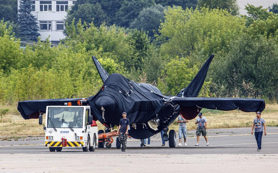 Hidden under tarpaulin, a prospective Russian fighter jet is seen being towed to a parking spot before its presentation at the Moscow international air show in Zhukovsky outside Moscow, Russia, Thursday, July 15, 2021.