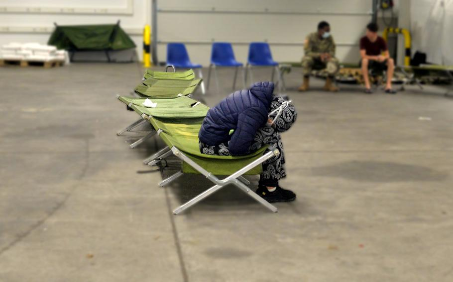 An Afghan woman sits alone in the medical area of a warehouse that has been transformed into a processing center for evacuees on Rhine Ordnance Barracks in Kaiserslautern, Germany, Aug. 30, 2021. Many of the Afghans who are being temporarily housed at the Army facility are suffering from depression and survivor guilt for those they left behind in Afghanistan, medical staff say.