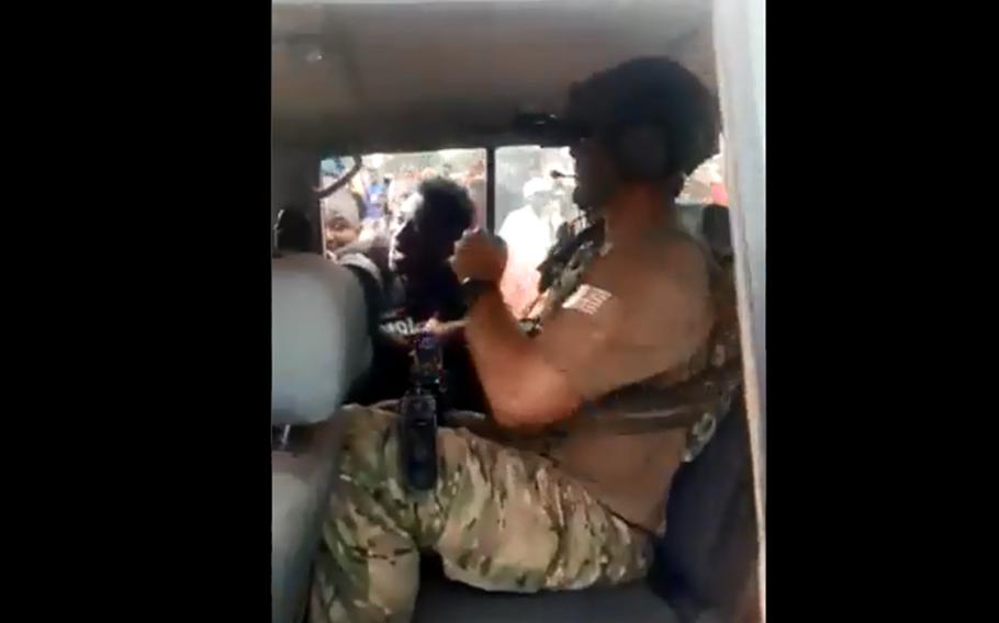 A large crowd surrounds a car carrying U.S. special operations troops on an assignment in Guinea, as shown in this screenshot from a video posted on Twitter. A military coup forced the U.S. team to cancel its training mission in the country.