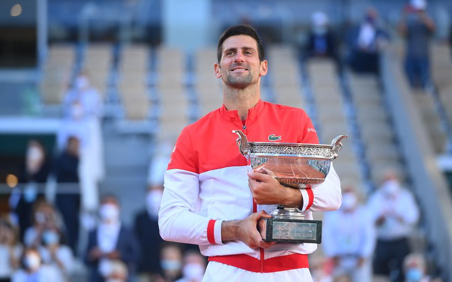 """Novak Djokovic enjoys a moment with the trophy after defeating Stefanos Tsitsipas 6-7, 2-6, 6-3, 6-2, 6-4 on Sunday in Paris to win the French Open and claim his 19th Grand Slam title. The victory gives Djokovic a second """"career"""" Grand Slam, meaning he has won each of the sport's four majors at least twice during his career."""