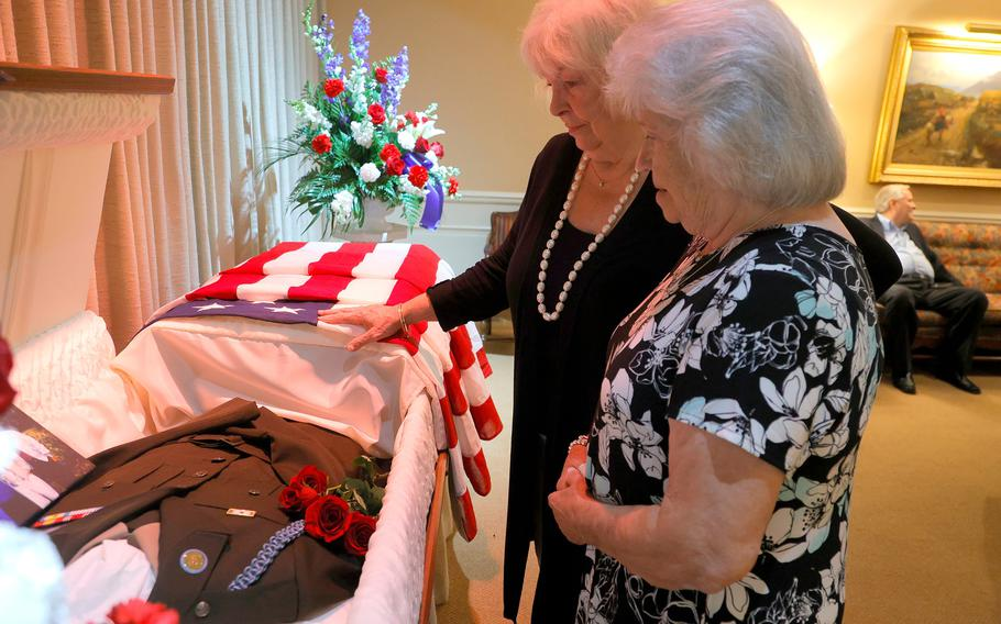 Patricia Ozybko, middle, and Helen Hoogacker-Fennell, sisters of U.S. Army Pfc.  Phillip Hoogacker, talk about him while viewing his Army uniform and pictures in his casket before the funeral service for Phillip Hoogacker at R.G. & G.R. Harris Funeral Home in Livonia, Mich., on July 23, 2021.