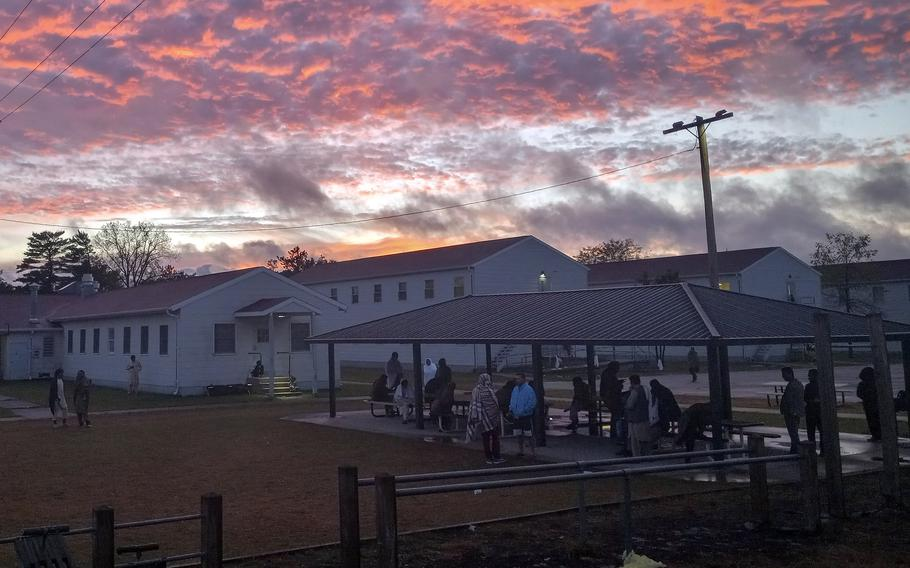 Afghan evacuees gather to talk Sept. 24, 2021, as the sun sets over Fort McCoy, Wis., where they are waiting to be resettled.