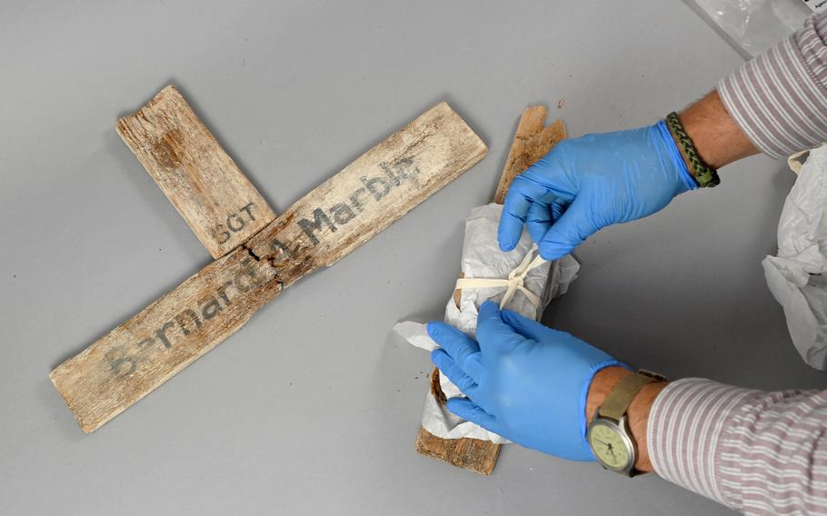Owen L. Conner, curator for the National Museum of the Marine Corps, unwraps pieces of a wooden cross bearing the name of Sgt. Bernard A. Marble, 28, of Massachusetts, one of more than 1,000 Marines who died in the 1943 battle for Tarawa.