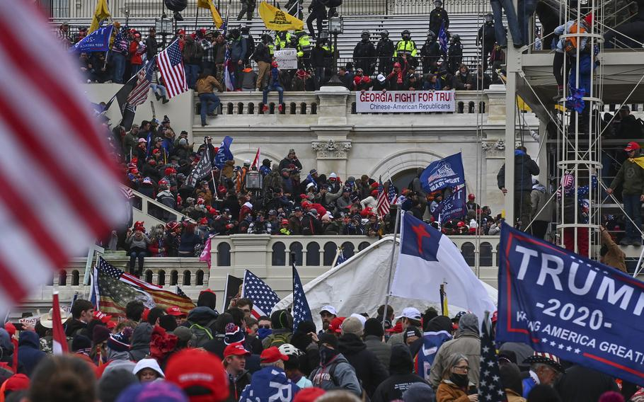 Participants in a mob take over the inaugural stage at the Capitol on Jan. 6.