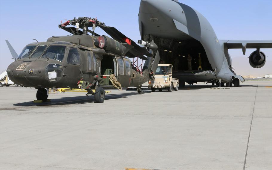 Aerial porters work with maintainers to load a UH-60L Black Hawk helicopter into a C-17 Globemaster III at Bagram Airfield, Afghanistan, as the U.S. military draws down forces and equipment in the country, June 16, 2021.