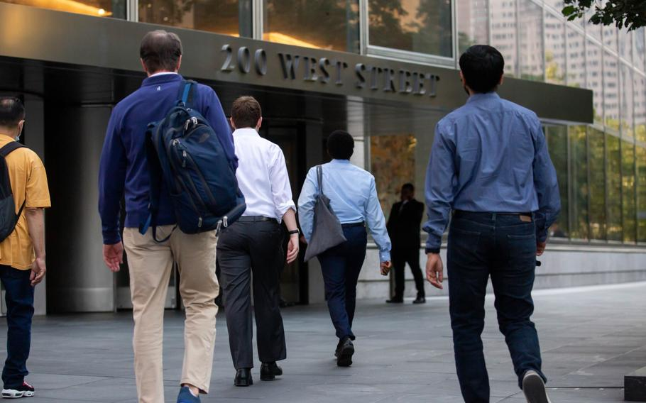 Office workers walk toward the Goldman Sachs headquarters in New York on July 22, 2021.