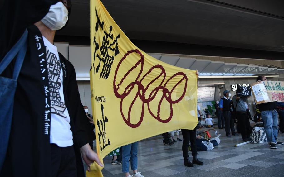 Protesters hold up a banner and shout near National Stadium just hours before the official start of the Tokyo Olympics, Friday, June 23, 2021.