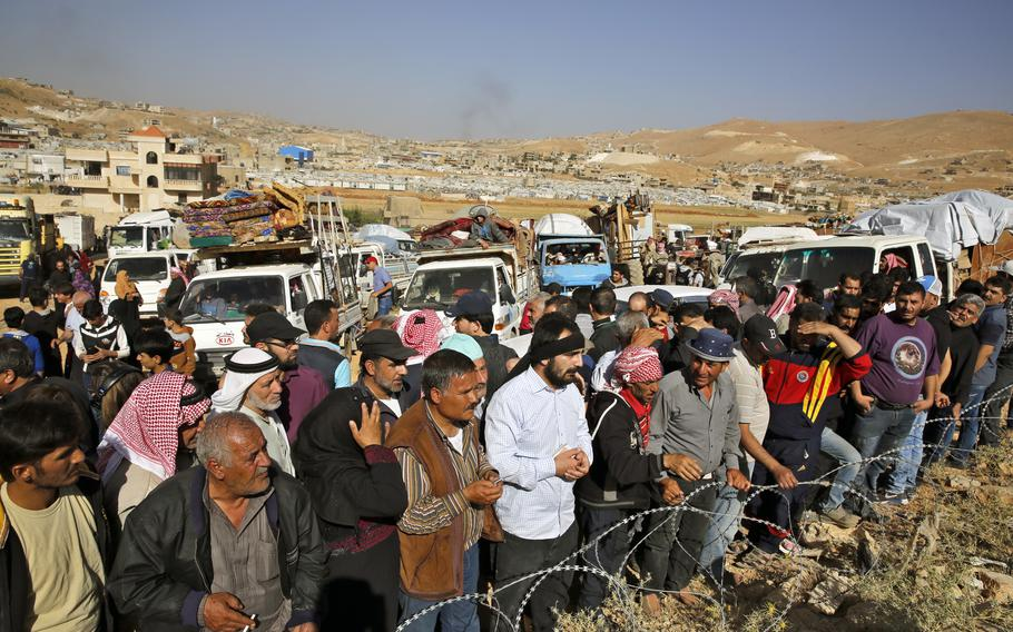 Syrian refugees gather in and near their vehicles getting ready to cross into Syria from the eastern Lebanese border town of Arsal, Lebanon, on June 28, 2018.  A number of Syrian refugees who returned home have been subjected to detention, disappearance and torture at the hands of Syrian security forces, proving that it still isn't safe to return to any part of the country, Amnesty International said in a new report released Tuesday, Sept. 7, 2021.