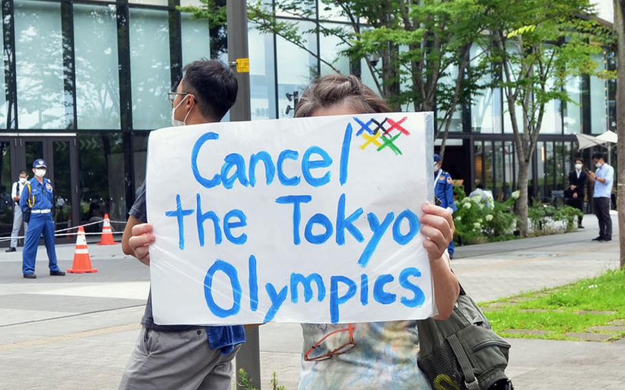 A handful of protesters call for canceling the Tokyo Olympics outside a private torch relay ceremony in Tachikawa, Japan, Monday, July 12, 2021.