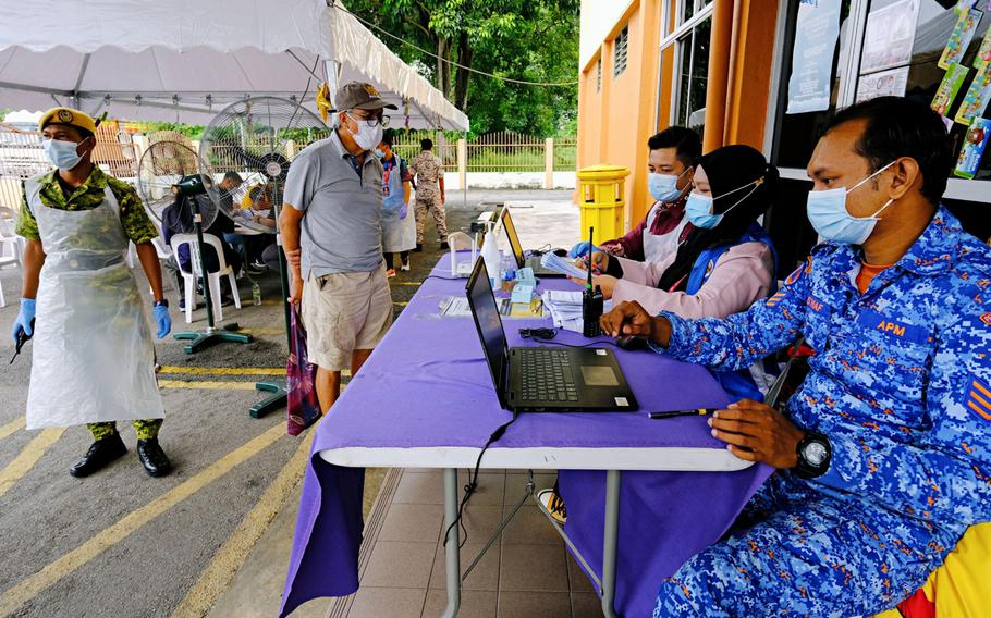 Health workers register people to receive a dose of the Sinovec COVID-19 vaccine at a vaccination center set up at the Pandamaran Sports Hall in Port Klang, Selangor, Malaysia, on May 20.