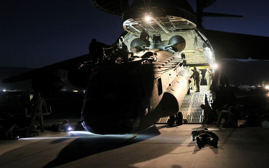 Aerial porters work with maintainers to load a CH-47 Chinook into a C-17 Globemaster III in Afghanistan, June 16, 2021.