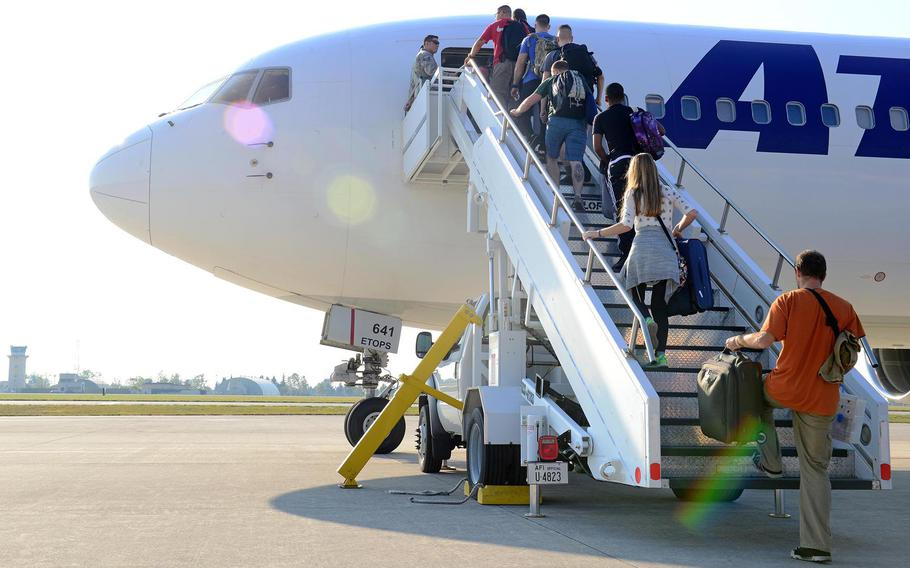 Airmen and their families board a plane at Aviano Air Base, Italy, in 2016. Because of the coronavirus pandemic, the Air Force is letting members accrue two months of extra leave to use over the next three years.