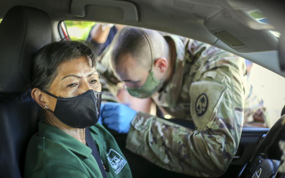 Spc. Michael Marsh, of the Guam National Guard, administers a COVID-19 vaccine to a member of the community at the Port Authority of Guam, June 2, 2021.