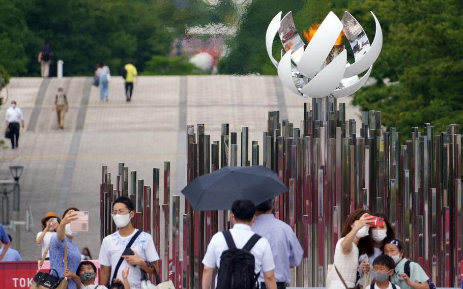 People pose with the Olympic cauldron in Ariake, Tokyo, July 30, 2021.