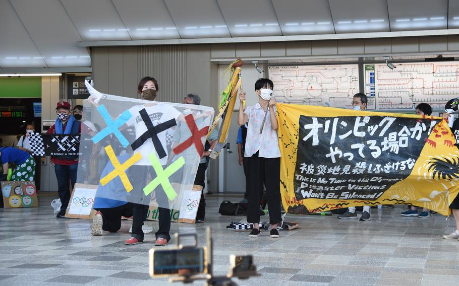 Anti-Olympics protesters hold up banners near National Stadium just hours before the official start of the Tokyo Games, Friday, June 23, 2021.