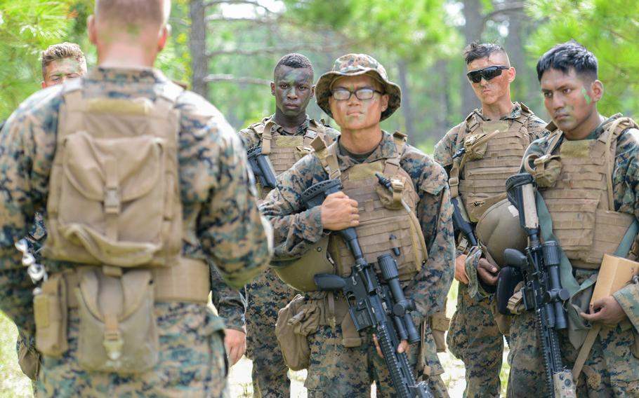 Marine infantry students listen to their combat instructor's feedback after conducting an ambush during training at Camp Lejeune, N.C., on Aug. 27, 2021. The students were practicing an ambush during an initial infantry training pilot program meant to drastically change the way the Corps trains its infantrymen. The pilot program expands infantry training from nine to 14 weeks and places Marines in 14-person squads under a single instructor.