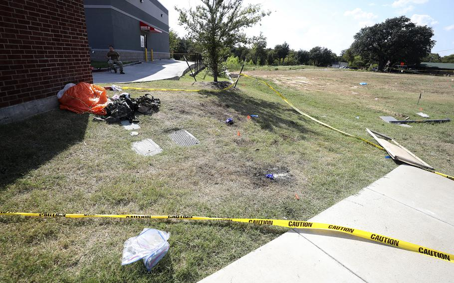 A parachute and other items remain outside an Ole Donut where one pilot landed after ejecting from a military training jet before it crashed Sunday, Sept. 19, 2021, in Lake Worth, Texas. The jet crashed Sunday in a neighborhood near Fort Worth, Texas, injuring the two pilots and damaging three homes but not seriously hurting anyone on the ground, authorities said.