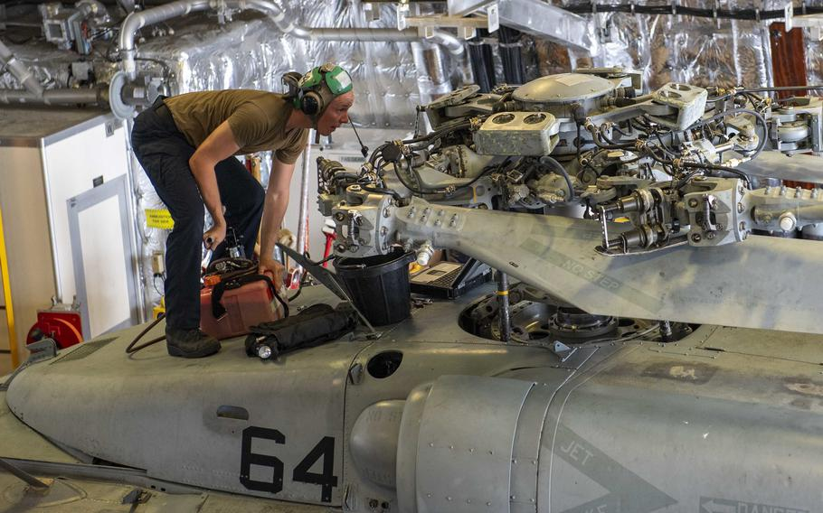 Petty Office 3rd Class David Smerdon pumps hydraulic fluid into one of Helicopter Sea Combat Squadron (HSC) 21's MH-60S Sea Hawk helicopter. Speeding the parts and supplies sailors like him need is the mission of the new Norfolk-based Maintenance Operations Center.