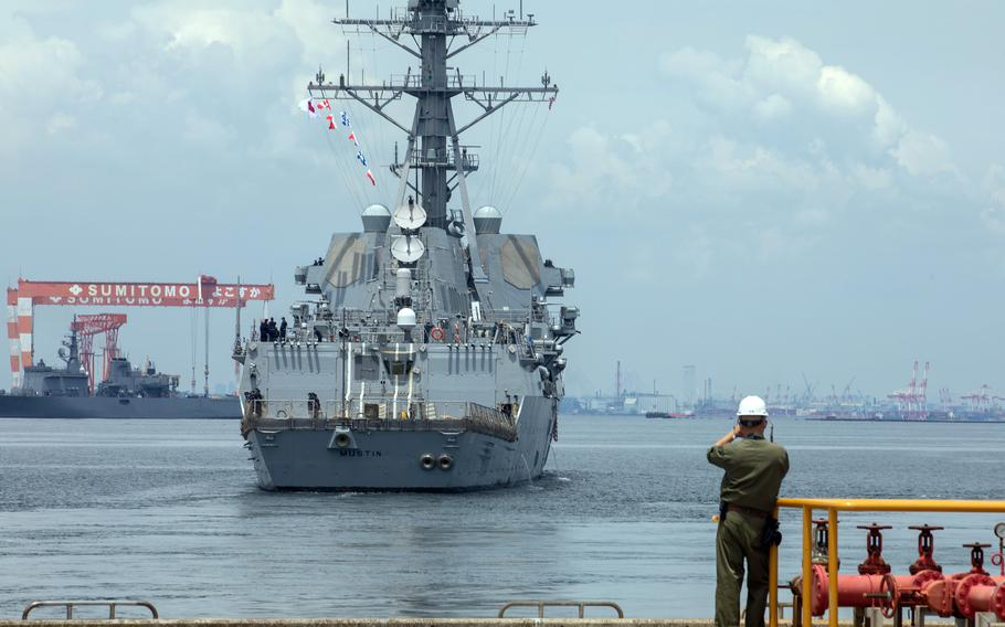 The guided-missile destroyer USS Mustin steams away from Yokosuka Naval Base, Japan, June 22, 2021.