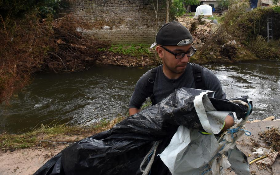 Senior Airman Calixto Rodriguez of Spangdahlem Air Base, Germany, removes trash from the banks of the Nims River in Rittersdorf on July 31, 2021. More than two dozen airmen from the base volunteered to help clean up the river in the aftermath of last month's severe flooding in western Germany.