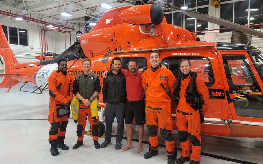 In this photo provided by the U.S. Coast Guard, kayaker Cyril Derreumaux, in shorts, poses with the Coast Guard helicopter crew that rescued him off the California coast in San Francisco on Saturday, June 5, 2021.
