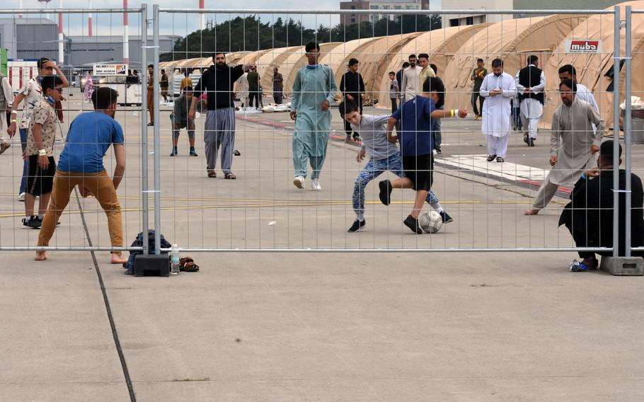 Men and boys play a game of soccer inside temporary living facilities set up for evacuees from Afghanistan on Ramstein Air Base, Germany, Aug. 23, 2021.