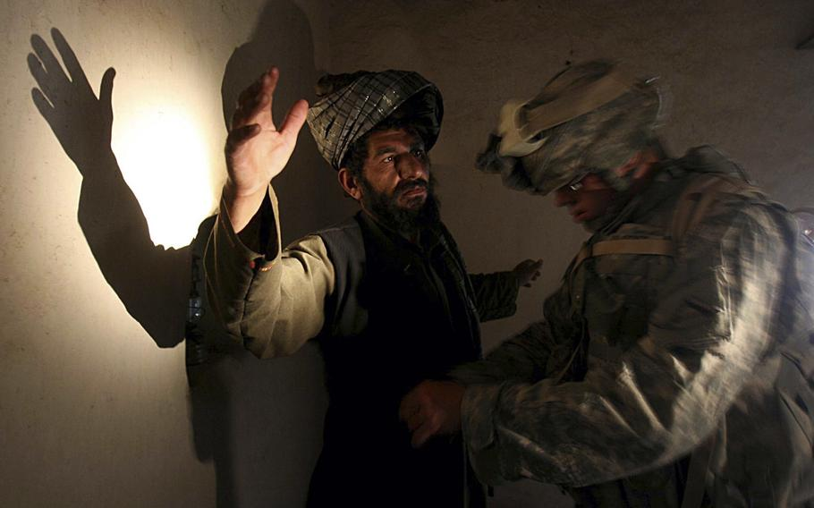 A U.S. soldier of Company B, 4th Infantry Regiment frisks an afghan man in his house during a search operation in Sinan village in Zabul province, southeastern Afghanistan.