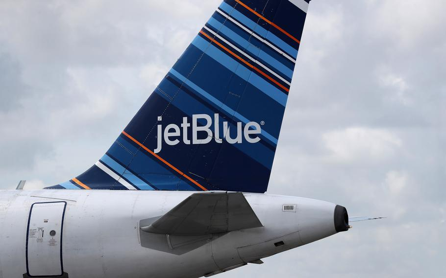 The tail of a JetBlue plane is seen as it prepares to take off in 2020. A woman on a JetBlue Airways Corp. flight from Miami to Los Angeles yelled at a flight attendant and slammed into his body, almost knocking him into a lavatory, according to the FAA. She is one of many passengers who have behaved badly on jets, often to little or no consequence to themselves.