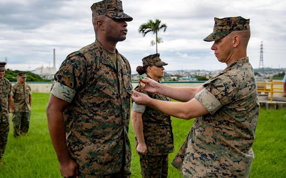 Master Gunnery Sgt. Ronald Thomas and his wife, Master Sgt. Sara Thomas, receive the Navy and Marine Corps Commendation Medal at Camp Courtney, Okinawa, June 15, 2021. The pair was honored for heroic actions during a flash flood last year at Ta-Taki Falls.