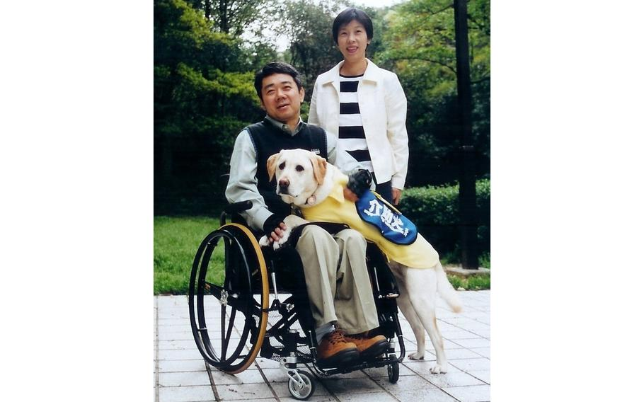 Yoshitomo Kimura, 61, with his wife and his first service dog, Cynthia.