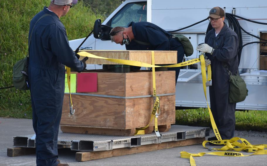 Blue Grass Chemical Activity personnel strap the last of the mustard overpacked projectiles onto a tray for loading into an enhanced on-site container.