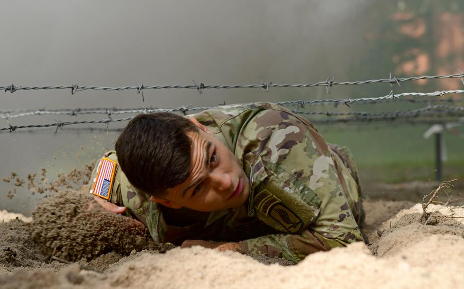 First Lt. Jim Schooley, from the 173rd Airborne Brigade, low crawls under barbed wire while participating in the obstacle course circuit during the U.S. Army Europe and Africa Best Warrior competition in Grafenwoehr, Germany, Aug. 9, 2021. Schooley won the best officer competition.