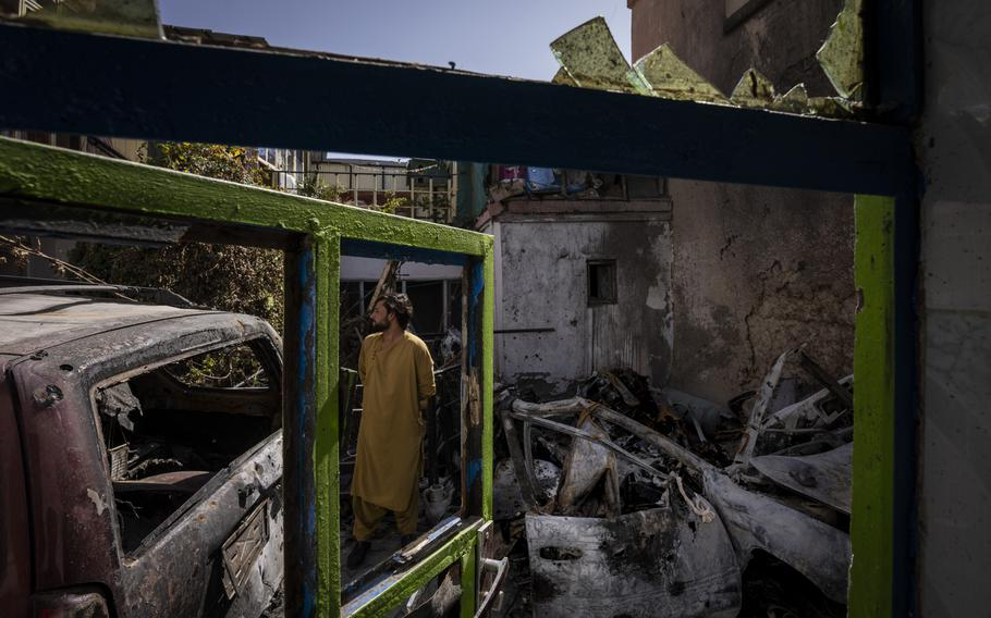 In this Sept. 13, 2021, file photo, an Afghan inspects the damage of Ahmadi family house in Kabul, Afghanistan. A U.S. drone strike killed 10 members of the family, including seven children. On Sept. 18, 2021, they demanded Washington investigate who fired the drone and punish the military personnel responsible for the strike, said Emal Ahmadi, whose 3-year-old daughter Malika was killed Aug. 29 when the U.S. hellfire missile struck his elder brother's car.