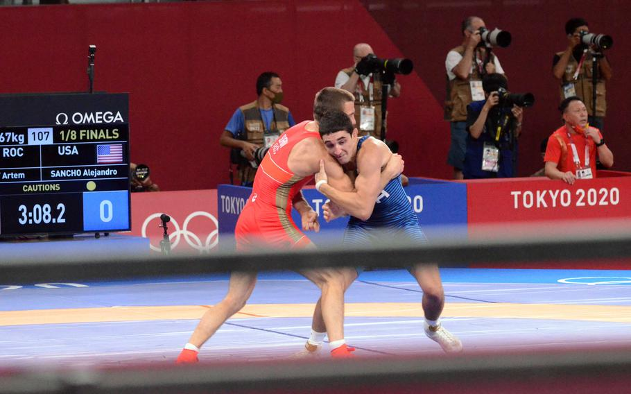 Army Spc. Alejandro Sancho, in blue, grapples with Russian Artem Surkov during their Olympic 67 kg Greco-Roman wrestling bout in Makuhari, Japan, Tuesday, Aug. 3, 2021.