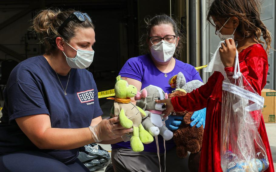 USO volunteers offer stuffed toys to an evacuee from Afghanistan as she arrives at Naval Air Station Sigonella, Italy, Aug. 28, 2021.