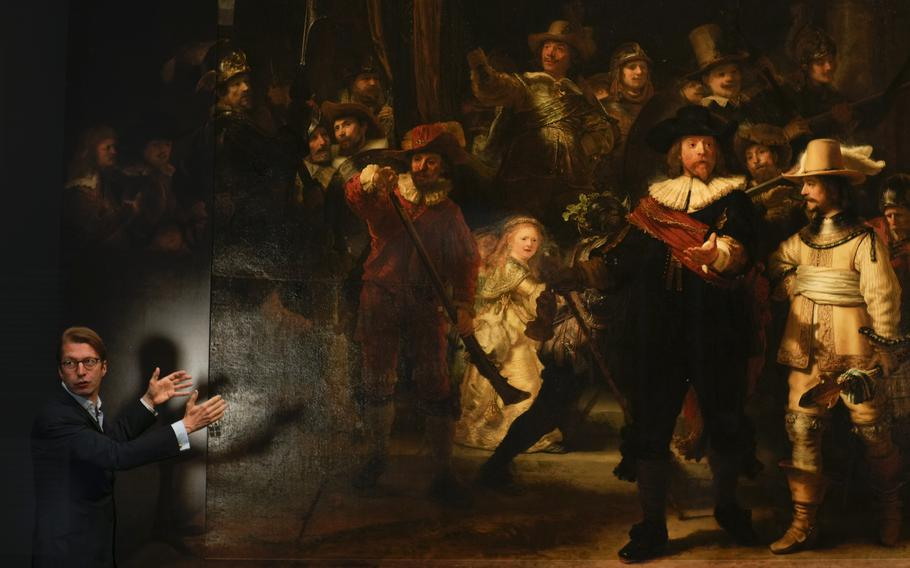 Museum director Taco Dibbits explains how Rembrandt's biggest painting the Night Watch just got bigger with the help of artificial intelligence in Amsterdam, Netherlands, Wednesday, June 23, 2021. Right above Dibbits, left, one of the added parts is seen, the Dutch national museum and art gallery reveals findings from a long-term project to examine in minute detail Rembrandt van Rijn's masterpiece the Night Watch.