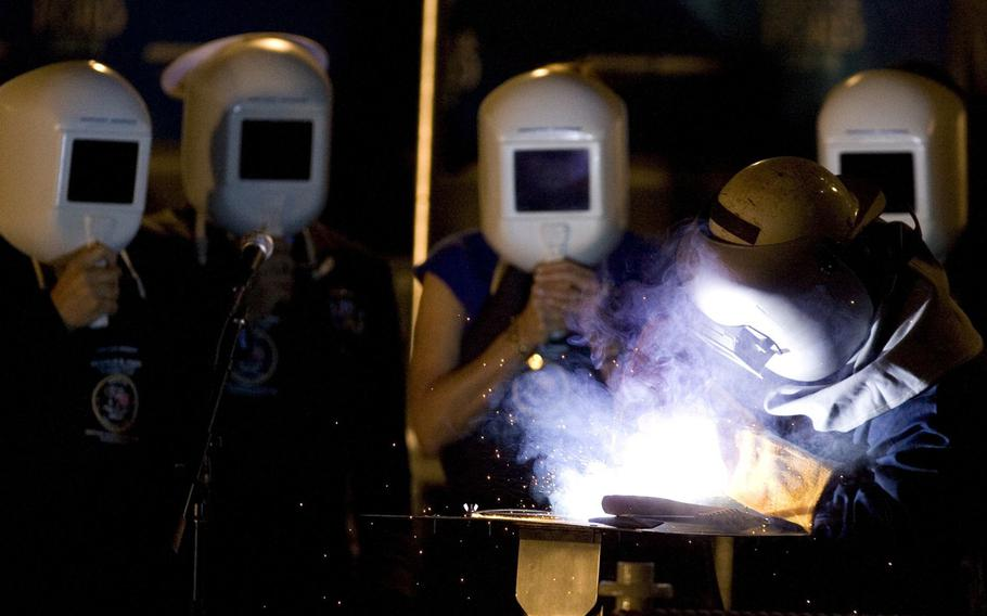 Robert Bowker welds the initials of the ship's sponsor, Susan Ford Bales onto the keel Saturday, Nov. 14, 2009, during the keel laying and authentication ceremony for the Gerald R. Ford carrier (CVN 78) at Northrop Grumman Corp.'s Newport News shipyard.