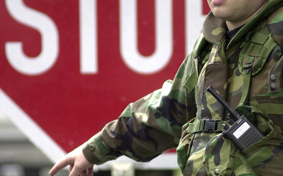 An airman from the 469th Security Forces Flight directs cars approaching Rhein-Main Air Base, Germany, to stop for a search on Sept. 12, 2001.